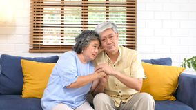 Senior asian couple comforting each other from depressed emotion while sitting on sofa at home living room, old retirement. Lifestyle royalty free stock photo