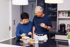 Senior Asian couple grandparents cooking together while woman is feeding food to man at the kitchen. Long lasting relationship Stock Photos