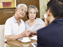 Senior asian couple meeting a sales rep. Senior asian couple appear to be confused after reading a proposal Royalty Free Stock Photos