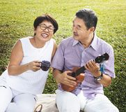 Senior Asian couple playing music in a park. stock image