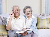 Senior asian couple. Reading a book together at home Royalty Free Stock Photos