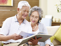 Senior asian couple reading a book together Stock Images