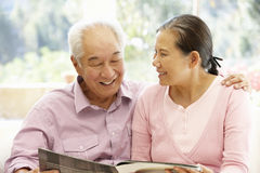 Senior asian couple reading magazine Stock Photo