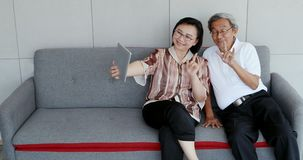 Senior Asian couple selfie their photo by tablet. stock footage