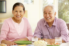 Senior asian couple sharing meal at home Royalty Free Stock Image