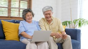 Senior asian couple shopping online by using laptop computer and credit card at home living room, Retirement people technology. Lifestyle stock image