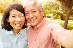 Senior Asian Couple Taking Selfie In Park Together Stock Image