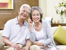Senior asian couple talking on cellphone Stock Photo