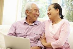Senior Asian couple using laptop Stock Photo