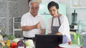 Senior Asian couple using a laptop while cooking in kitchen at home. 70s Elderly man and woman in relationship