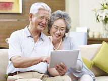 Senior asian couple using a tablet computer together Royalty Free Stock Photo