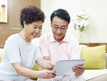 Senior asian couple using tablet computer together Royalty Free Stock Photo