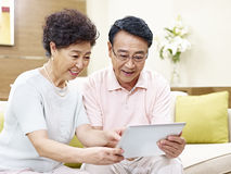 Senior asian couple using tablet computer together Royalty Free Stock Images