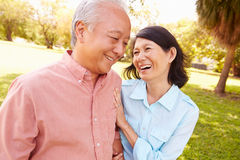 Senior Asian Couple Walking Through Park Together Stock Image