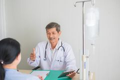 Senior Asian doctor, Thumbs up. smile and eye contact with female patient. Expressing delight with report treatment results stock photo