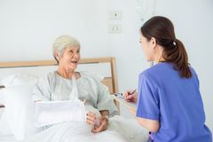 Senior asian female patient smiling with nurse royalty free stock photography