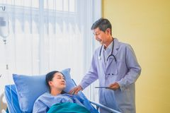 Senior asian male doctor visiting and talking with middle-aged female patient on Ward. royalty free stock images