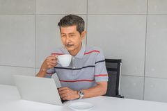 Senior asian man has a white mustache...Hand holding a coffee mug, Look at the laptop computer stock photo