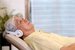Senior asian man listening headphones whlie laying on sofa in home living room with happiness, retirement lifestyle and technology. Senior asian man listening stock photography