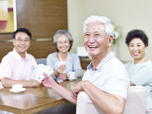 Senior asian man in playing cards with friends Stock Image