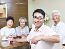 Senior asian man in playing cards with friends stock photos