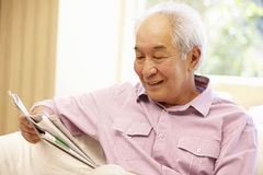 Senior Asian man reading newspaper Royalty Free Stock Images