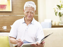 Senior asian man relaxing reading a book at home Stock Image