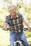Senior Asian man riding bike in park Stock Photography