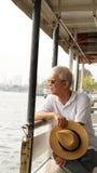 Senior Asian man riding  a ferry boat to cross Chaopraya river i Royalty Free Stock Image