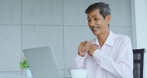 Senior man using laptop and excited about it. stock footage
