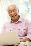 Senior Asian man using laptop Stock Image