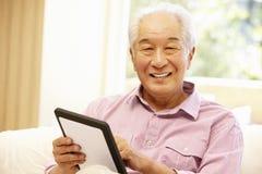 Senior Asian man using tablet Stock Photo