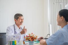 Senior Asian physician, Sitting and smile eye contact with female patient. Expressing delight with the treatment results in doctors office stock images