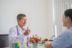 Senior Asian physician, Thumbs up. smile and eye contact with female patient. Expressing delight with the treatment results in doctors office royalty free stock image