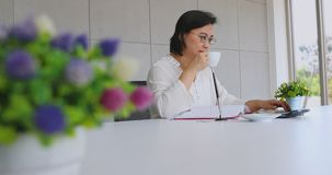 Senior Asian woman accounting in the office. Senior Asian woman drinking coffee and using a calculator to account for her income expenditure, blurred flower at stock footage