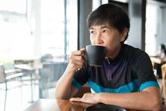 Senior Asian woman with coffee in cycling jersey. Portrait of a senior Asian woman in cycling jersey hold a cup of coffee Royalty Free Stock Photography