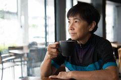 Senior Asian woman with coffee in cycling jersey. Portrait of a senior Asian woman in cycling jersey hold a cup of coffee Stock Photography