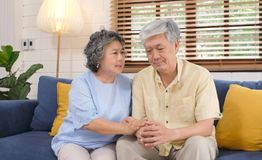 Senior asian woman comforting her husband from depressed emotion while sitting on sofa at home living room, old retirement. Senior asian women comforting her royalty free stock photography