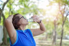 Senior asian woman drinking water bottle after work out exercising royalty free stock images