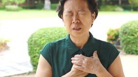 Senior Asian woman having heart attack, chest pain stock video
