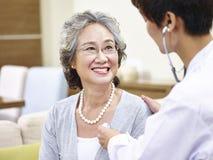 Senior asian woman having a physical check Royalty Free Stock Photos