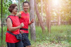 Senior asian woman with man or personal trainer jogging running in the park. Happy senior asian women with men or personal trainer jogging running in the park stock image