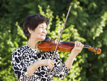 Senior Asian Woman Playing Violin outdoors Royalty Free Stock Photos