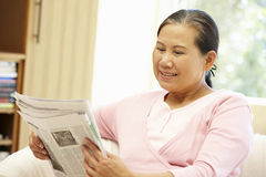 Senior Asian woman reading newspaper Stock Photo