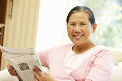 Senior Asian woman reading newspaper Stock Photo