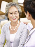 Senior asian woman talking to a medical worker Stock Image