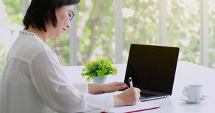 Senior Asian woman writing note on notebook. stock video footage