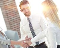 Senior assistant looks at the handshake business partners. The concept of partnership Royalty Free Stock Photo