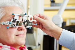 Senior with astigmatism and trial. Senior women with astigmatism and trial frame at the optician royalty free stock photography