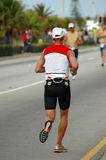 Senior athlete. An elderly caucasian senior triathlete running on the road participating in an Ironman triathlon competition Stock Image